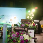 Staggered floral arrangements in briefcases, at different heights, flanked each side of the stage.